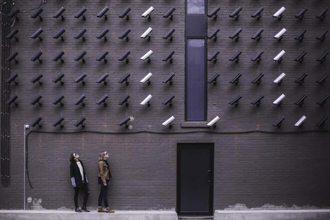 wall full of cameras with two girls watching